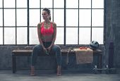 foto of sitting a bench  - Looking off to the side a fit woman in workout gear is sitting on a bench listening to music - JPG