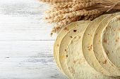 picture of whole-wheat  - Stack of homemade whole wheat flour tortilla on wooden table background - JPG