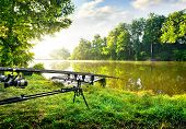 picture of rod  - Fishing rods near calm river in the morning - JPG