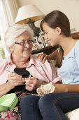 foto of granddaughter  - Grandmother Showing Granddaughter How To Crochet At Home - JPG