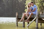 stock photo of jetties  - Young Romantic Couple Sitting On Wooden Jetty Looking Out Over Lake - JPG
