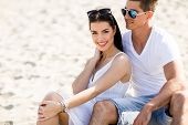 image of couple sitting beach  - Young couple sitting on a sandy beach - JPG