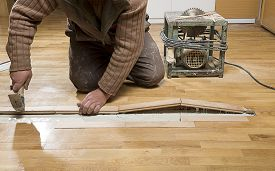 stock photo of leak  - Manual worker fixing wooden floor ruined from moisture and water leak - JPG