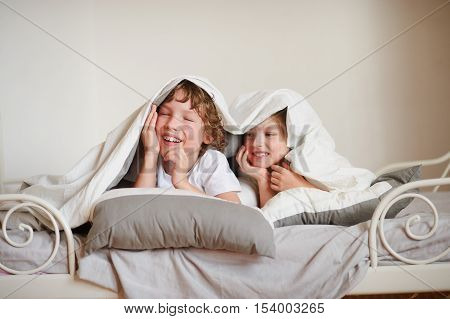 Two children brother and sister squirmy on the bed in the bedroom. They with a smile look out from under a blanket.