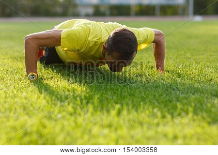 Morning warm-up sporty athletic guy. Man doing push-ups