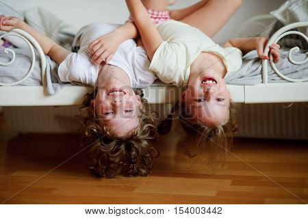 The children boy and girl naughty on the bed in the bedroom. They lie side by side their heads hanging off the bed. Children is very amused.