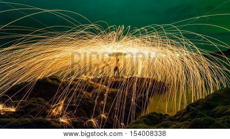 Man Cast Fire Steel Wool On Hill Rock Beach