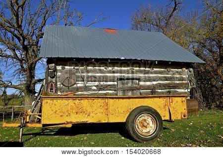 An old rusty manure spreader is converted into a trailer and parked in front of a log cabin.