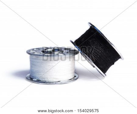 Black and white sewing bobbins, isolated on white background.