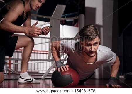 Doing well. Concentrated bearded guy doing press-ups with help of special fitness ball while his trainer counting time.