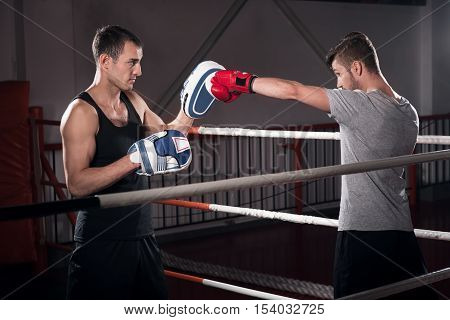 Direct hook. Side view of young bearded man standing on ring and working on boxing hook together with his trainer in special pad.