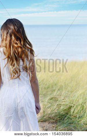 back of young girl looking at ocean