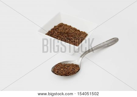 Flax seed in a ceramic container and in the metal spoon isolated on a white background