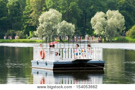 TSARSKOYE SELO, SAINT - PETERSBURG, RUSSIA - JULY 25, 2016: People on the ferry on The Great Pond. The historical Ferry line connects The Catherine Park near Admiralty with the Hall on the Island