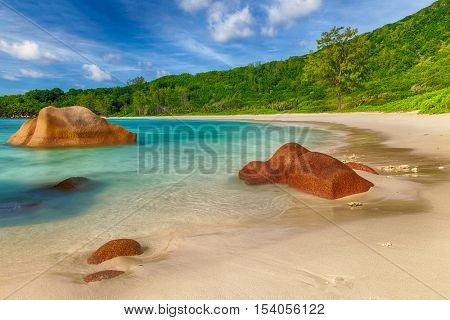 Beautifully shaped granite boulders in the turquoise sea (daytime long exposure technique) at Anse Coco, La Digue island, Seychelles