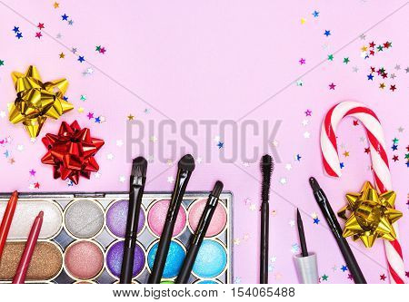 Makeup for festive party. Color glitter eyeshadow, mascara, eyeliner, lip liners, lip gloss, makeup brushes and applicator with candy cane, gift wrap bows and confetti on pink background. Copy space