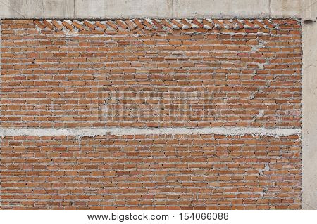 Weathered red brick wall with concrete seam.