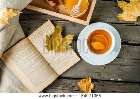 Cozy autumnal mood, warm autumn. A cup of hot tea with lemon and ginger on a rustic table, plaid, yellow leaves, honey and a book to read. Top view
