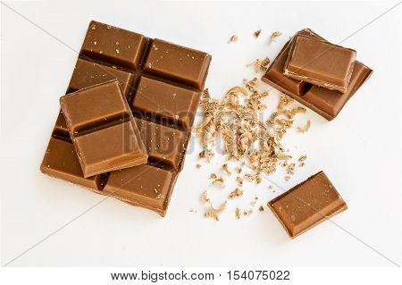 milk cooking chocolate broken into blocks arranged on a white background