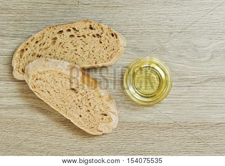 two slices of Ciabatta bread and a bowl of extra virgin oil on a wooden textured background
