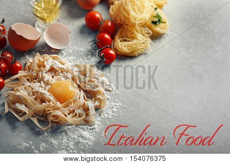 Homemade pasta with yolk on table. Text ITALIAN FOOD on gray background. Traditional meal concept.
