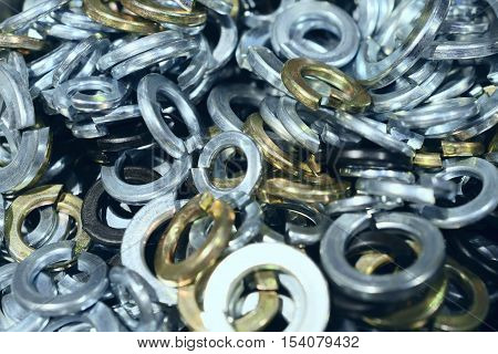 Many shims arranged as background. Metal fasteners, scattered in plastic cells.