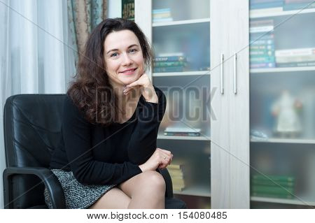 The girl sits on a chair in the home office. The bookcase in the background.