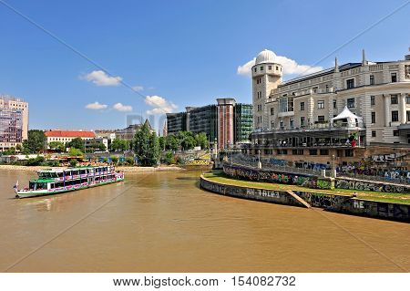 VIENNA AUSTRIA - JUNE 6: Touristic boat goes by Danube river in Vienna on June 6 2016. Vienna is a capital and largest city of Austria.