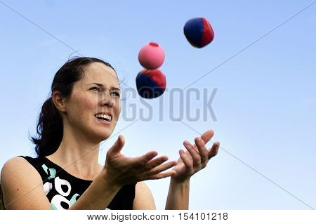 Young woman juggler is juggling balls with blue sky background.