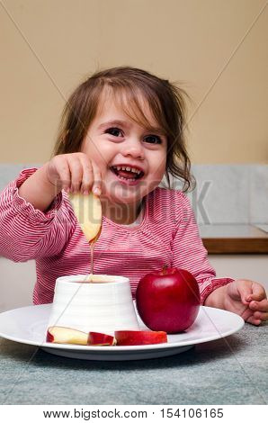 Little Jewish Girl Dipping Apple Slices Into Honey