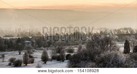 skyline of small village in winter with fuming chimneys