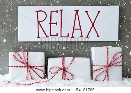 Three Christmas Gifts Or Presents On Snow. Cement Wall As Background With Snowflakes. Modern And Urban Style. Card For Birthday Or Seasons Greetings. Label With English Text Relax