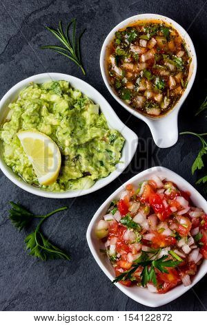 Traditional mexican Latin American sauces - avocado sauce Guacamole, tomato sauce Salsa, chili sauce Pebre in white bowls on stone slate background