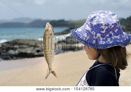 Little Girl Looks At A Fish On A Hook