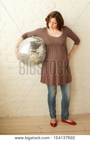 Pregnant woman stands home interior with big silver ball