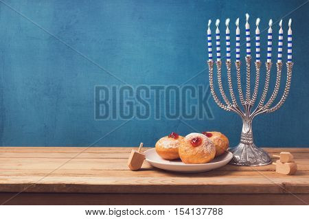 Hanukkah holiday sufganiyot and menorah on wooden table over vintage background