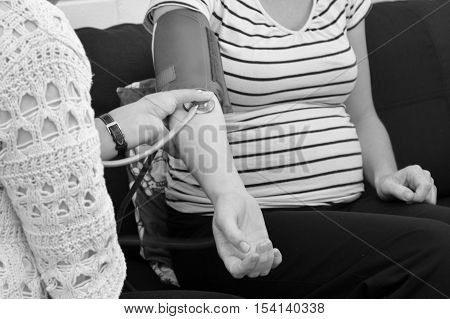 CABLE BAY NZ - APR 02 2014:Midwife checks pregnant woman blood pressure.In pregnancy it's the fetal heart that builds up the fetal blood pressure to drive its blood through the fetal circulation. close up (BW)