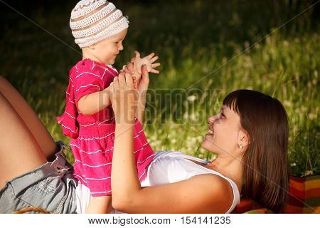 Young woman with her little 1 year old daughter are having fun in the park