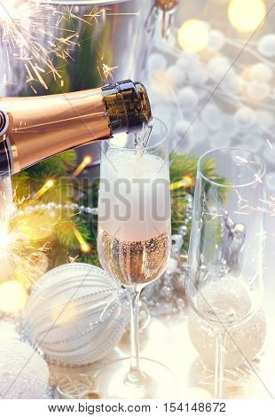 Christmas and New Year celebration with champagne. Holiday dinner table setting with Christmas decoration and sparkling wine. Champagne pouring