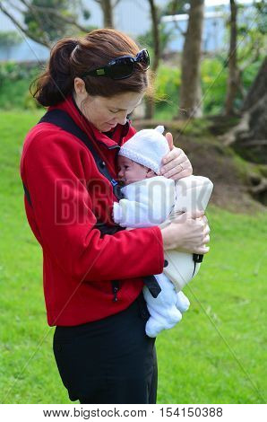 Mother Carry Newborn Baby On Baby Carrier