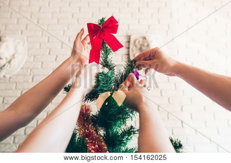 Happy family decorating Christmas tree, close-up. Couple preparing for winter holidays. New year, party, joy concept