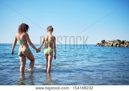 Woman and girl walk holding hands into the sea, rear view.