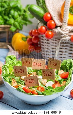 Unhealthy Vegetable salad with preservatives on old wooden table