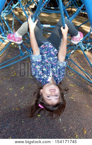 Little Child Paly On Spider Web Bar In Outdoor Playground