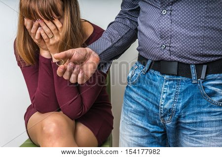 Disappointed man returning the wedding ring to his wife - divorce concept