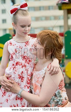 Smiling mother sits squatted and embrace daughter that stands near her at playground in courtyard.