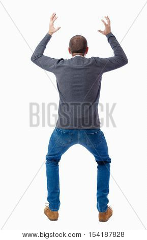 Back view of shocked  man .   upset young guy in jeans and shirt. Rear view people collection.  backside view of person.  Isolated over white background. A guy in a gray sweater terrified waving hands