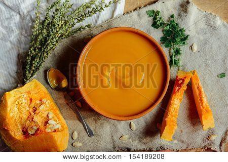 Pumpkin Porridge And Pumpkins On Black Wooden Table. Plate Pumpk