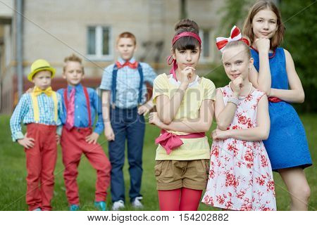 Three girls propping chins at foreground and three boys behind them out of focus stand outdoor on summer day.