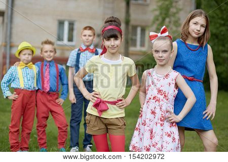 Three girls at foreground and three boys behind them out of focus stand outdoor on summer day.
